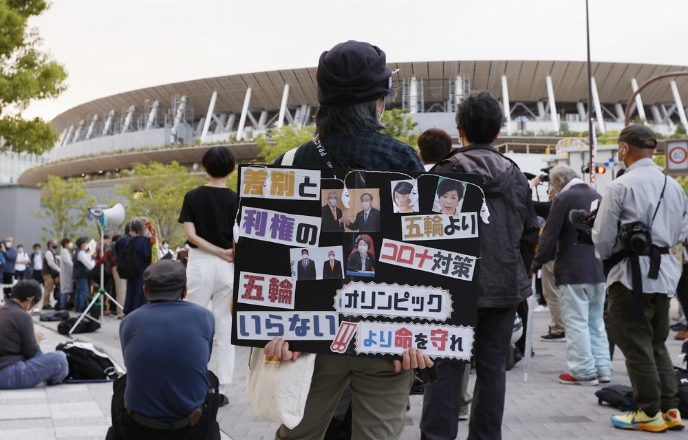 陸上のテスト大会が行われている国利競技場周辺で、東京五輪中止を訴える人たち=5月9日