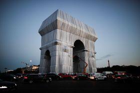 現代美術家の故クリストさん夫妻の遺作として、作業員により布で梱包されるパリの凱旋門=17日(ロイター=共同)