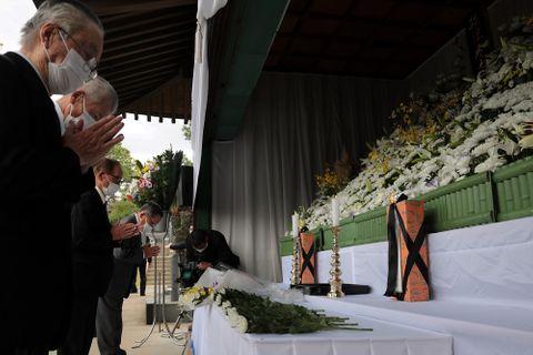 献花し、手を合わせる参列者=佐世保東山海軍墓地