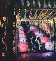 ライトアップされた和傘の石段を下りる親子=小鹿野町の小鹿神社