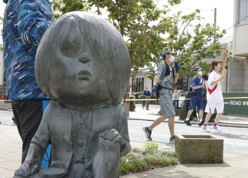 「水木しげるロード」を走る聖火ランナー。左は「鬼太郎」の像=21日午前、鳥取県境港市