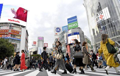 東京・渋谷のスクランブル交差点を歩く人たち=21日午後