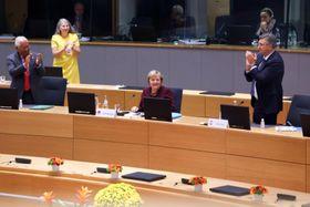 22日、EU首脳会議で拍手を受けるドイツのメルケル首相(中央)=ブリュッセル(ゲッティ=共同)