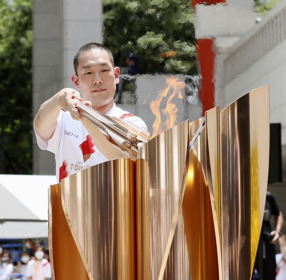 聖火皿に炎を移す歌舞伎俳優の中村勘九郎さん。全国をつないだ東京五輪の聖火リレーは121日かけて47都道府県を巡った=23日午後、東京都庁の都民広場(代表撮影)
