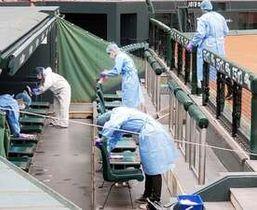 マツダスタジアムの一塁側ベンチを消毒する人たち(17日)