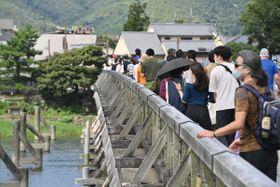 観光客らが行き交う渡月橋(19日午後、京都市右京区)