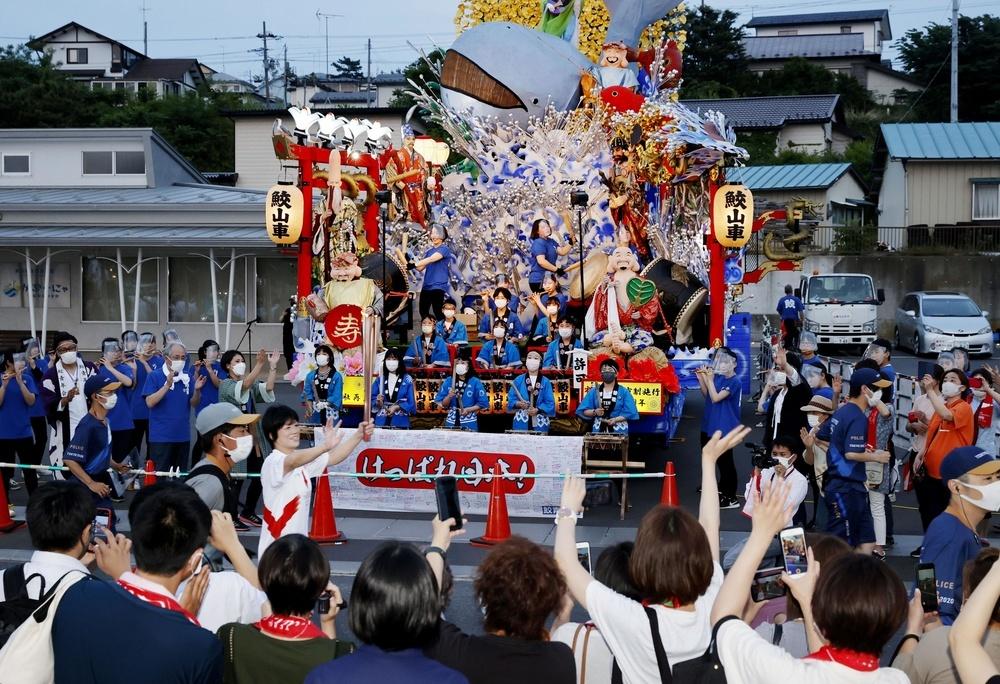 山車の前で笛や太鼓を演奏し、聖火ランナーを応援する地元住民ら=11日夕、青森県八戸市