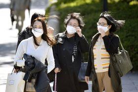 近畿で冬の訪れを告げる「木枯らし1号」が吹き、髪をなびかせ歩く人=23日午後、大阪市
