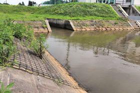 斜面に安全ネット(写真左)が設置された調整池=登米市迫町新田