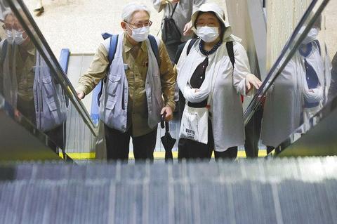 JR東京駅のエスカレーターで、難病の藤原佳世さん(右)を支えるように隣後方に立つ夫の康裕さん