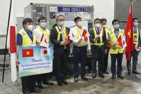 ワクチンの入ったコンテナの前で記念撮影する日本とベトナムの政府関係者ら=16日、ハノイ(共同)