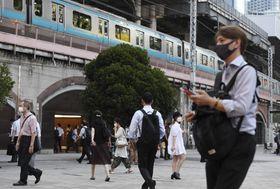 東京・新橋駅前を歩くマスク姿の人たち=28日午後