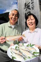 なれずしを販売する田中勝英さん(左)と真智子さん夫妻。勝英さんの手には大物の「尺アユ」=道の駅「あゆの里矢田川」