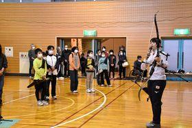 アーチェリーで使う道具について、子どもたちに解説する中村美樹選手(右)=鶴岡市小真木原総合体育館