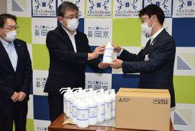 中小路健吾市長(右)にアルコール除菌液を手渡す楠田康之工場長