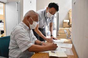 ワクチンパスポート申請書類に記入する市民(手前)=26日午後、宮崎市保健所