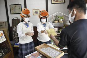 カクレクマノミの焼き印を入れたオリジナル残月を販売する長浜高校の生徒