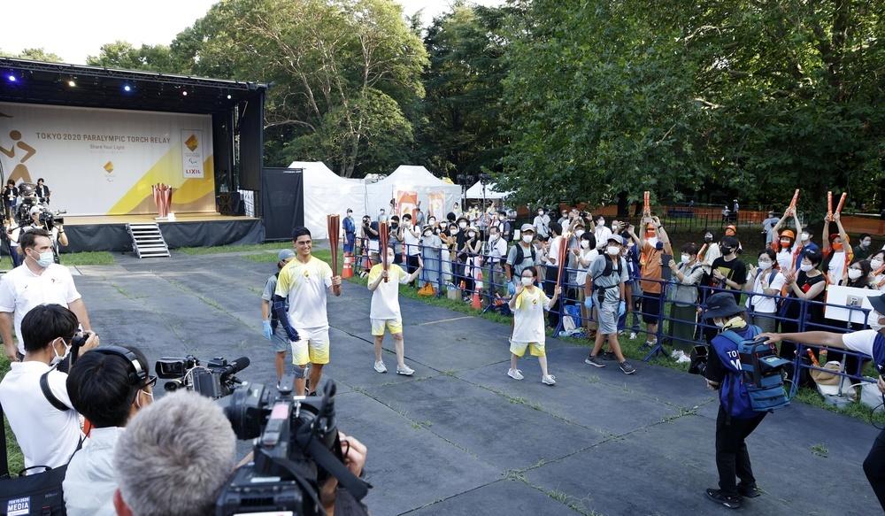 東京都世田谷区の砧公園で聖火のトーチを掲げるランナーら。24日に聖火台にともされ、大会を見守る=23日午後