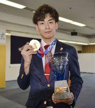 高松市役所で市民栄誉賞を授与され、記念写真に納まるフェンシング男子エペ団体の宇山賢さん=14日午前