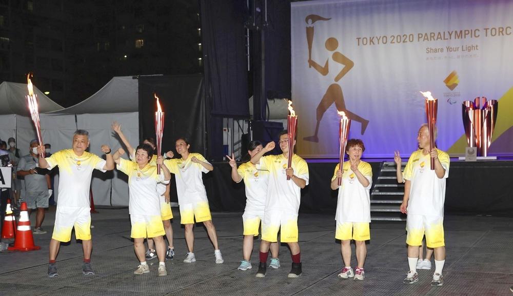 東京パラリンピックの聖火リレーは新型コロナウイルスの影響で公道走行中止となったが、ランナーらは聖火のトーチを手に笑顔を見せた=22日午後、東京都国分寺市