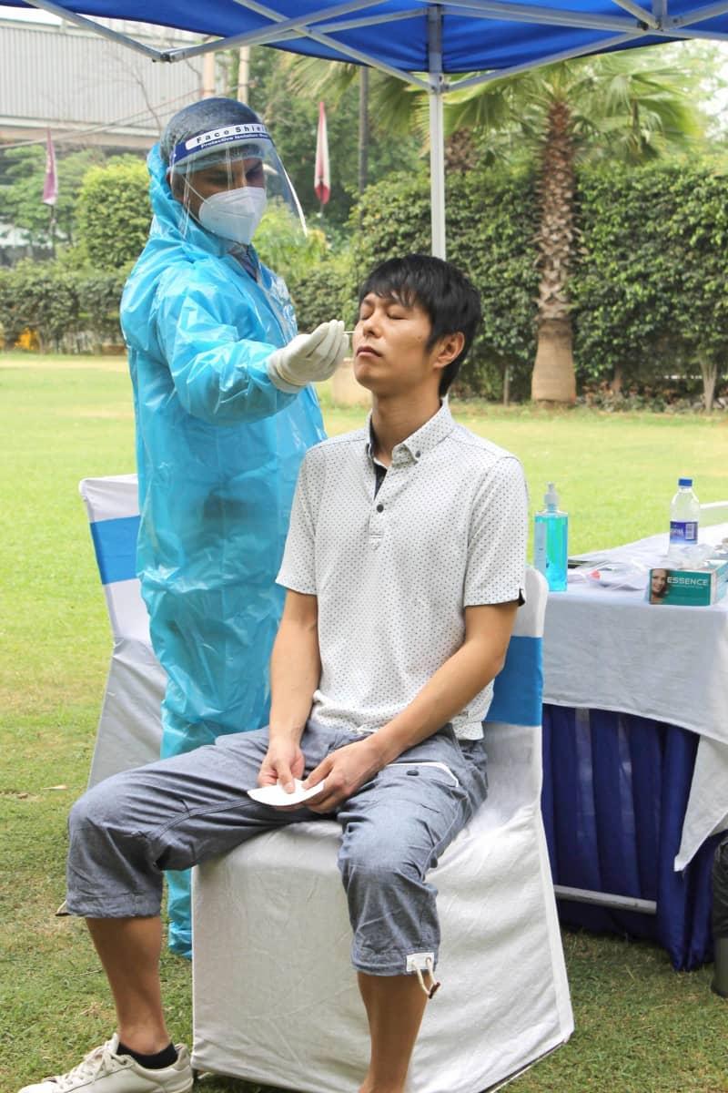 17日、インドの首都ニューデリー近郊のホテルでPCR検査を受ける日本人男性(共同)